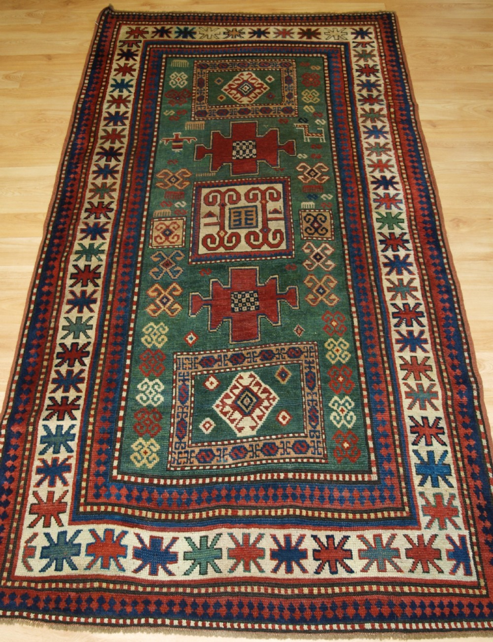 antique caucasian karachov kazak of rare green ground format 4th quarter 19th century