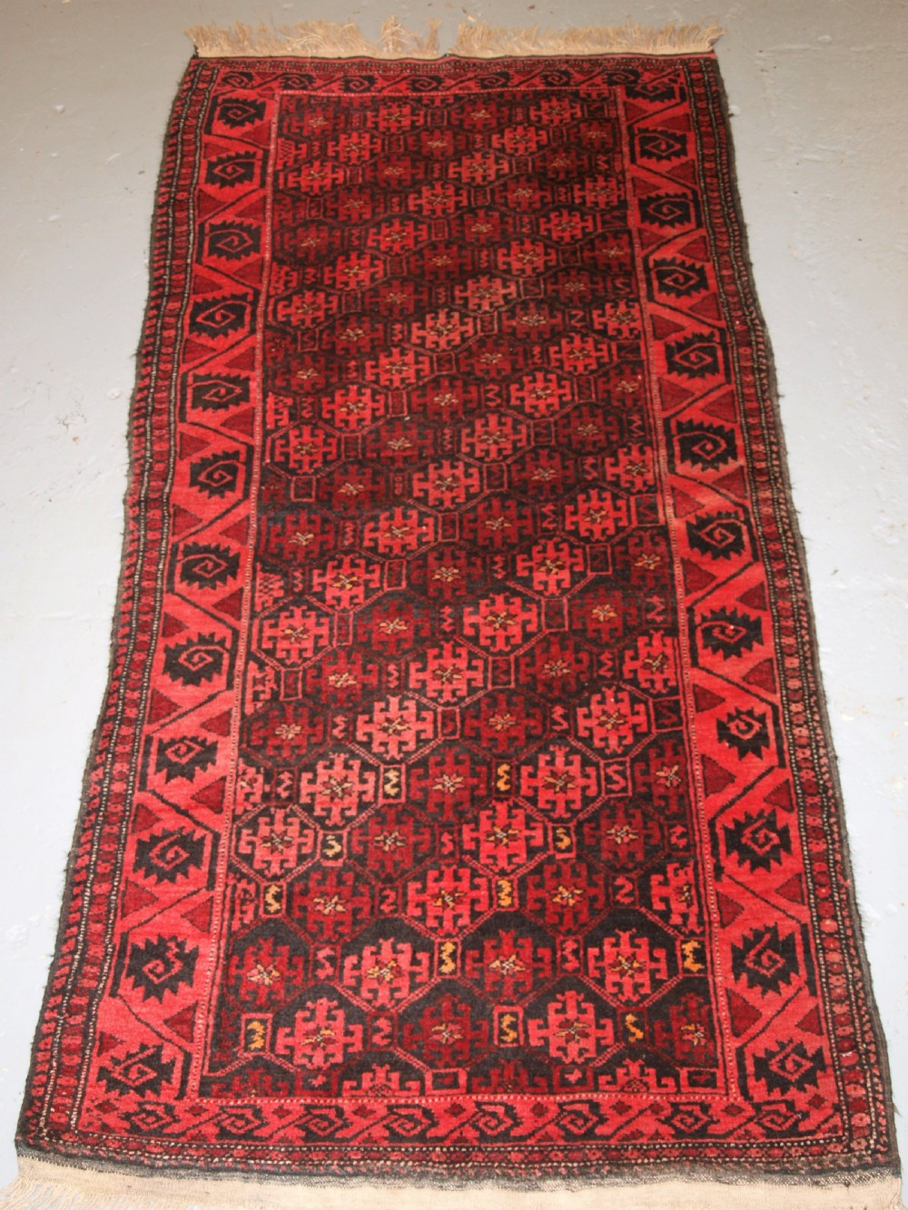 old afghan rug with repeat design curl leaf border rustic charm circa 1920